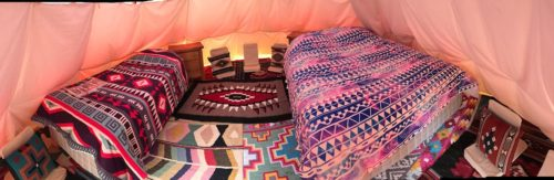 Each sleeping tipi is decorated in bright native american prints and decorative lights